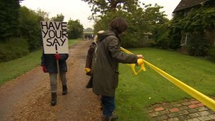 Protesters tie a yellow ribbon around part of the proposed development site.