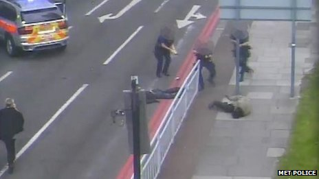 This image shows Michael Adebowale on the floor raising his gun