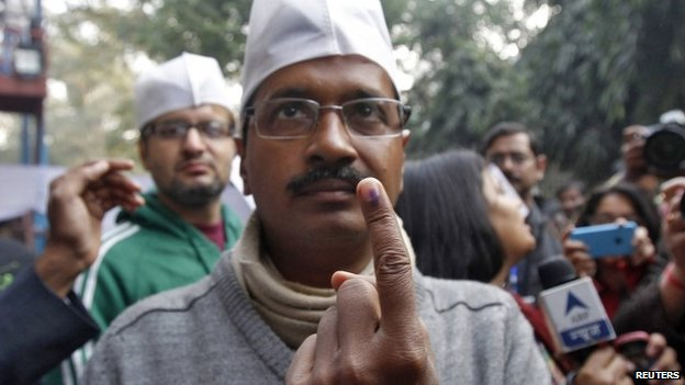 Arvind Kejriwal, leader of the newly formed Aam Aadmi (Common Man) Party, shows his ink-stained finger after casting his vote at a polling station in Delhi, 4 December2013
