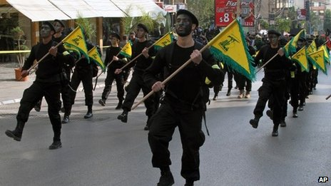 Hezbollah fighters hold their party flags, as they parade during a rally to mark the 13th day of Ashoura