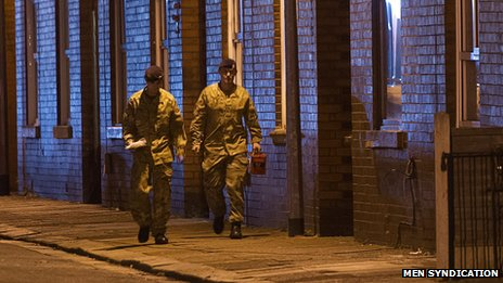 Two soldiers walk down a residential road at night