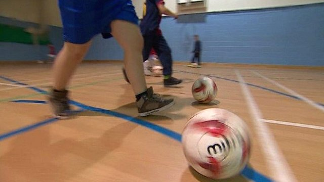 Boys practise football in a gym