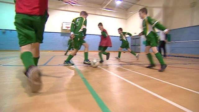 Boys playing football in a gym