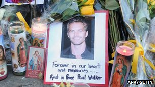 A photo of Fast & Furious actor Paul Walker is seen among flowers and candles left by fans at the site of the car accident in which he died north of California
