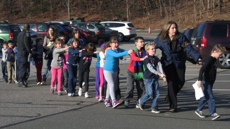 Connecticut State Police lead a line of children from the Sandy Hook Elementary School in Newtown, Connecticut, on 14 December 2012