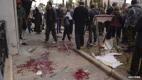 "Bloodstains are seen on the pavement as forces loyal to Syria""s President Bashar al-Assad and civilians gather at a site hit by rockets"