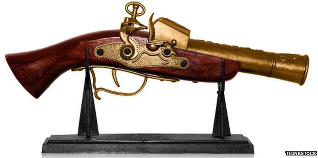 A stock image of a gun with a golden barrel