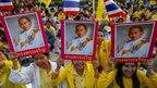 Well-wishers hold pictures of Thai King Bhumibol Adulyadej and wave Thai national flags as they gather to celebrate his 86th birthday near Klai Kangwon Palace, Hua Hin, Prachuap Khiri Khan province, 5 December 2013