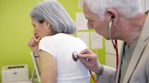 Lady coughing while doctor listens to her lungs with a stethoscope