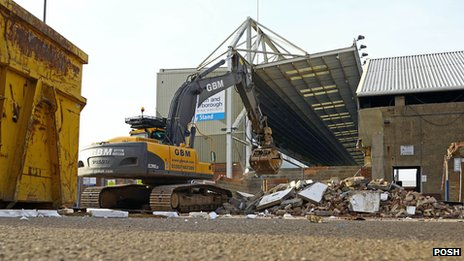 A digger works to demolish the stand