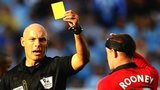 Referee Howards Webb brandishes a yellow card to Wayne Rooney