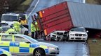 An overturned lorry lying on top of two damaged cars on an A-road