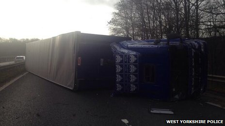 A lorry lies on its side on a dual carriageway