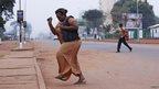 A woman runs from gunfire in Bangui December 5, 2013