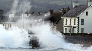 Waves hit a sea wall, sending spray high into the air