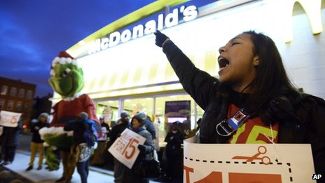 A woman protests wages outside a McDonalds in Chicago, Illinois on 5 December 2013