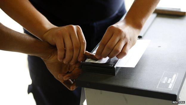 Serbian official takes migrant's fingerprints - file pic