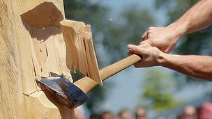 A man takes part in a Basque Country sports competition on cutting wood with an axe