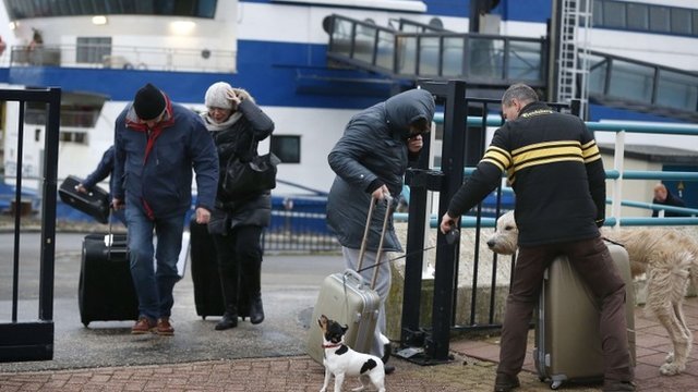 Passengers in the harbour of Harlingen, The Netherlands, struggle with the wind