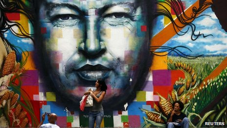 People stand around a mural depicting the late Venezuelan President Hugo Chavez in downtown Caracas  on 23 September, 2013
