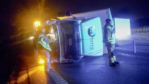 Rescuers stand by an overturned lorry in Ystad, southern Sweden. Photo: 5 December 2013