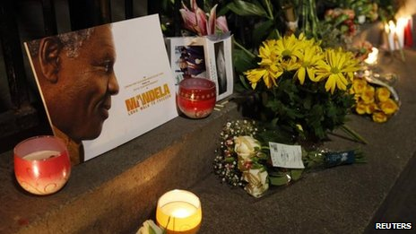 Flowers, candles and tributes are left in memory of Nelson Mandela outside the South African High Commission in London