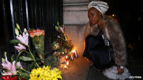 Lungi Morrison, the granddaughter of Archbishop Desmond Tutu, sings after lighting a candle for Nelson Mandela outside the South African High Commission in London 5 December 2013
