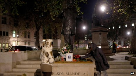 Flowers being placed at statue of Nelson Mandela in Trafalgar Square