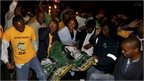 People chant slogans outside Nelson Mandela's house in Houghton