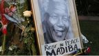 "A framed portrait of former president Nelson Mandela and flowers are placed outside Mandela""s Johannesburg home Friday, Dec. 6, 2013 after the freedom fighter passed away Thursday night after a long illness. ("