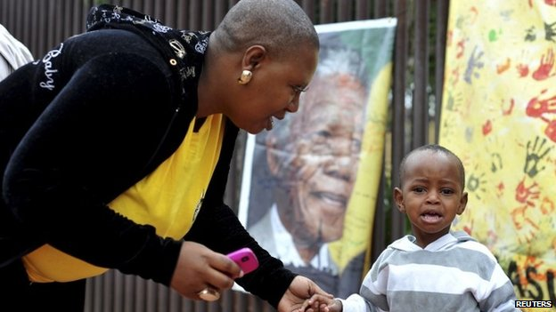Mother consoles son as they mourn outside Mandela house in Soweto