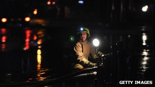 Firefighter pumps water from a flooded premises