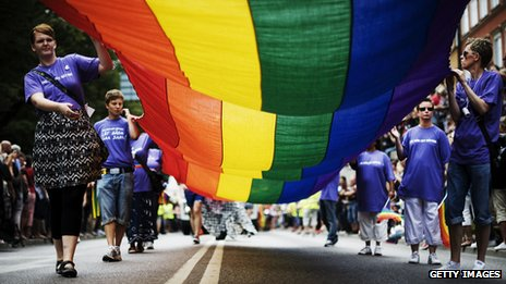 People unfurl a gay pride flag at the Stockholm Pride march