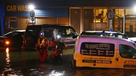 Coastguard rescue workers check vehicles in a flooded car wash during a storm surge in Great Yarmouth