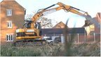 A mechanical digger begins to work on a building site