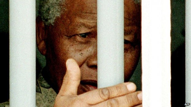 South African President Nelson Mandela stands on 27 March 1998 behind the bars of the former cell where he spent 18 years as a political prisoner on Robben Island