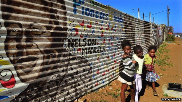 Children pose as they stand next to a mural of former South African President Nelson Mandela and other freedom fighters in the Orlando District of Soweto on 30 June 2013 in Johannesburg, South Africa