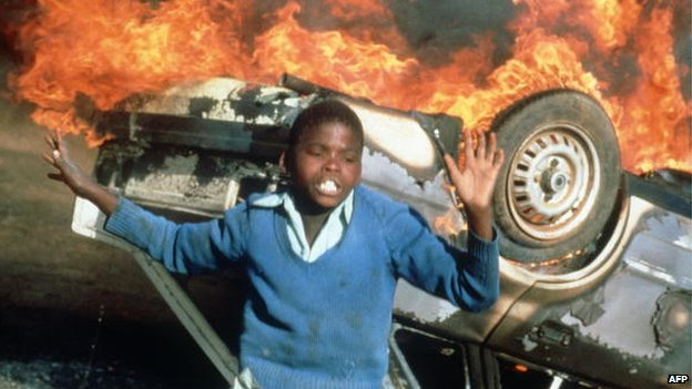 A South African boy pictured on 10 July 1985 in Duduza township by a car burnt during an anti-apartheid riot