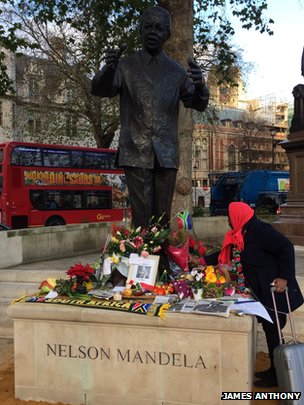 Woman laying flowers at Mandela statue
