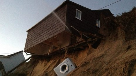 A beach chalet hanging over a beach after the ground beneath it collapsed