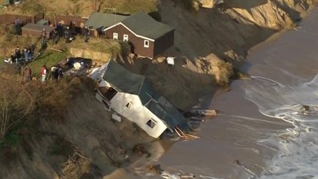 A collapsed beach chalet as seen from a helicopter