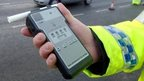 Police officer holds a breathalyser during Christmas Drink Drive campaign