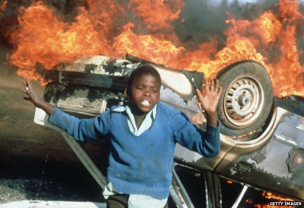 Boy in front of burning car, Duduza township 1985