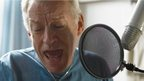 Mature man singing into a microphone