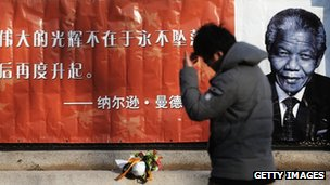 a man walks past a chinese poster of nelson mandela