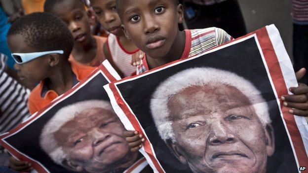 South African children hold placards showing the face of Nelson Mandela as they celebrate his life, in the street outside his old house in Soweto, Johannesburg, South Africa - Friday 6 December 2013