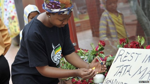 A woman lights a candle during a gathering of mourners on Vilakazi Street in Soweto, where the former South African President Nelson Mandela resided when he lived in the township, 6 December 2013