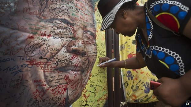 A well-wisher writes a message on a poster of Nelson Mandela on which she and others have written their messages of condolence and support, in the street outside his old house in Soweto, Johannesburg, South Africa Friday, 6 December 2013