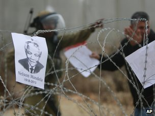 an israeli soldier gestures to a palestinian behind razor wire