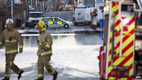 Firefighters and a police car separated by a flooded road